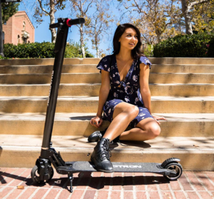 girl posing with her Swagtron scooter in front