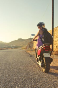 woman looking back to the camera while riding a bike