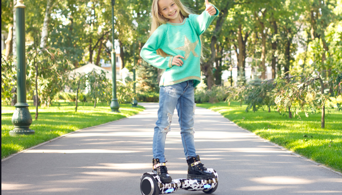 A little girl riding a hover board