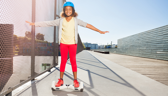 African girl in helmet riding hoverboard