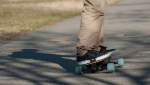 closeup of legs of man on electric skate board on the road
