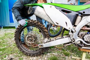mechanic fixing motocycle wheel