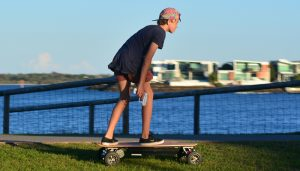 Young man rid on motorized skateboard