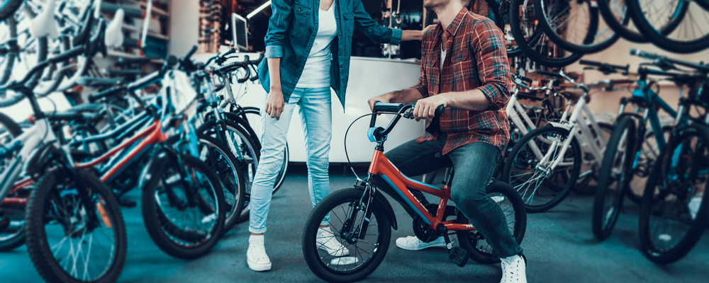 Happy Young Couple Chooses Kids Bicycle in Store. Woman In Denim Clothes Standing in Sport Cycle Shop Looks At Guy Wearing Checkered Shirt Sits on Children's Bike and Laughs