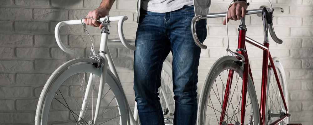 Man in jeans holding two bikes