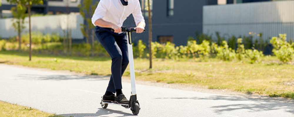 Businessman riding electric scooter