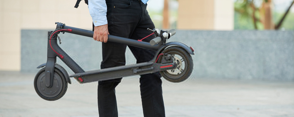 Man carrying electric scooter